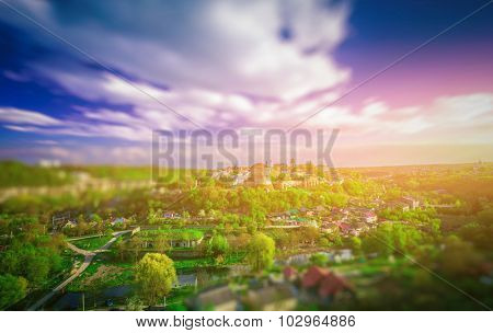 Amazing tilt shift effect view of village, green trees and colorful sky with clouds