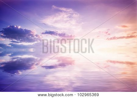 Abstract reflection in water. Reflected purple sky with clouds and sunset