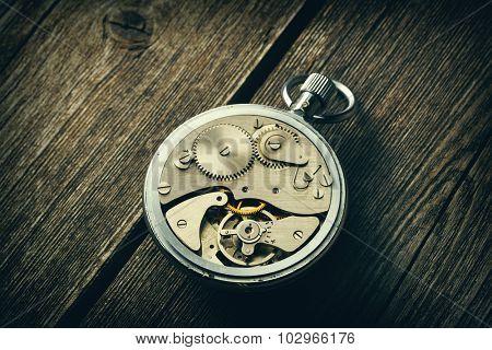 Clockwork mechanism over wooden background