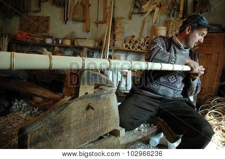 Carpenter Handcrafting A Wooden Alpenhorn