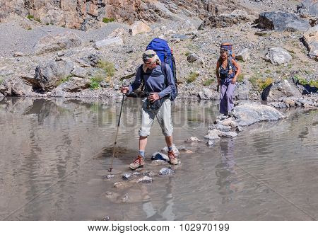 Man and woman crossing mountain river