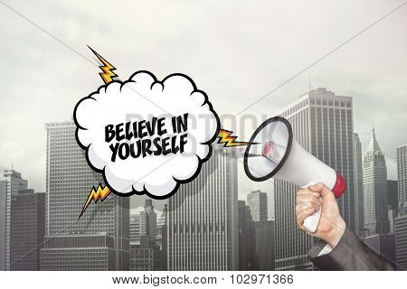Believe in yourself text on speech bubble and businessman hand holding megaphone