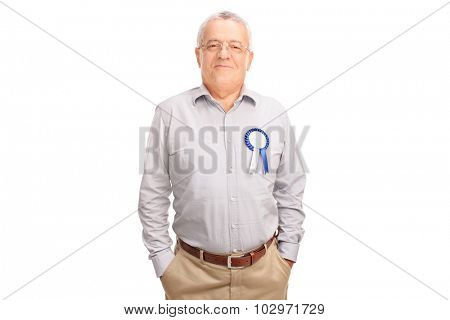 Proud senior gentleman posing with blue award ribbon on his shirt isolated on white background