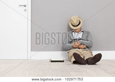 Senior sleeping on the floor with his hat covering his face and leaning against a wall next to a white door