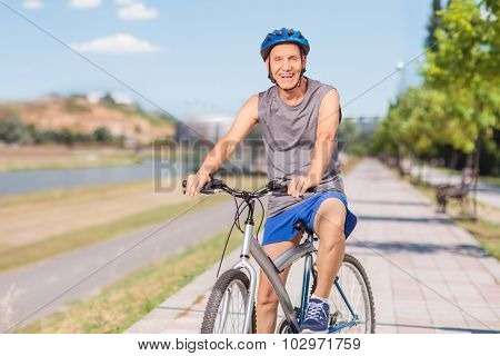 Cheerful senior man in sportswear posing with his bike on a sidewalk and looking at the camera