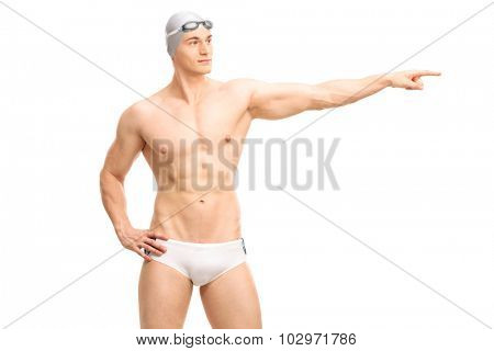 Young handsome male swimmer in white swim trunks pointing with his hand towards right isolated on white background