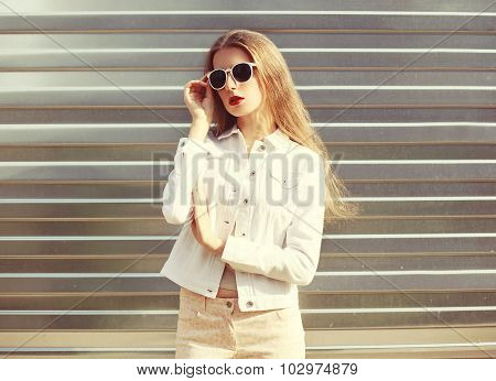Fashion Portrait Stylish Woman In Sunglasses And White Denim Jacket Over Metal Textured Background