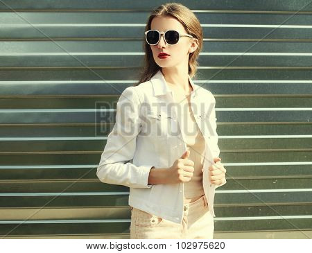 Fashion Pretty Woman In Sunglasses And White Denim Jacket Over Metal Textured Background