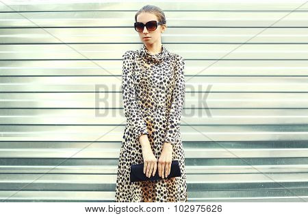 Fashion Pretty Young Woman In Sunglasses And Leopard Dress With Handbag Clutch Over Metal Background