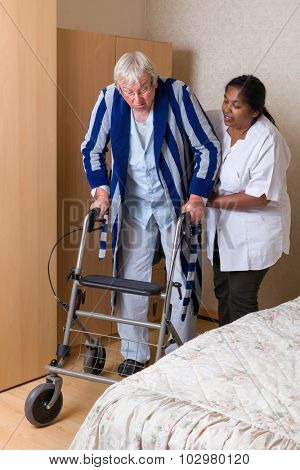 Elderly grandfather in nursing home using a rollator in his pajama