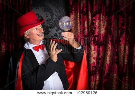 Senior magician performing on stage with a crystal ball