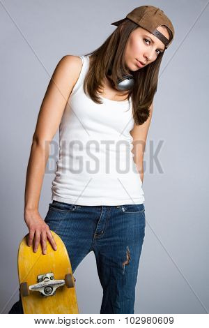 Pretty skater girl leaning on skateboard