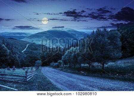 Fence Near Road Down The Hill With  Forest In Mountains At Night