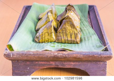 Dessert Wrapped In Banana Leaves On A Wooden Tray