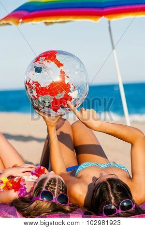 Young Mother And Daughter Looking At World Globe Ball.