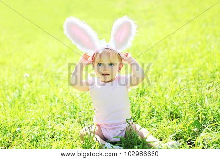 Happy Baby With Rabbit Ears Sitting On Grass In Sunny Summer Day
