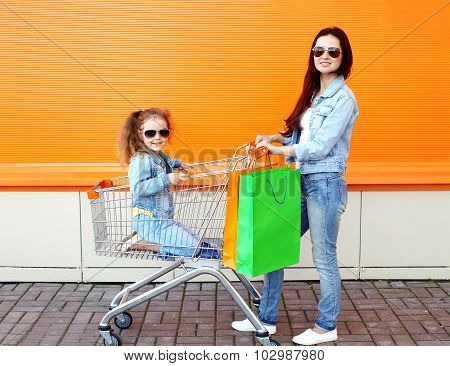 Happy Family Mother And Child With Trolley Cart And Colorful Shopping Bags