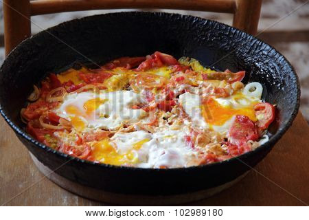Fried Eggs With Tomatoes In A Pig-iron Frying Pan