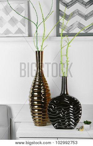 Modern vases on commode in room