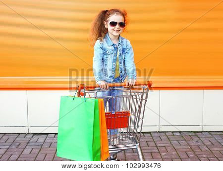 Happy Smiling Little Girl Child In Trolley Cart With Colorful Shopping Bags
