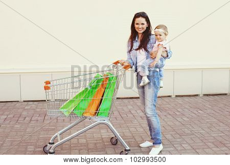 Happy Smiling Mother And Baby With Trolley Cart And Colorful Shopping Bags