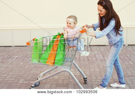 Happy Smiling Mother And Child With Trolley Cart And Colorful Shopping Bags Having Fun