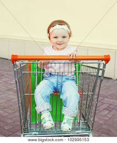 Portrait Cute Baby Sitting In Trolley Cart With Shopping Bags