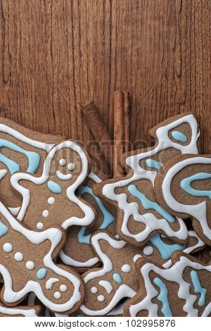 Tray of decorated gingerbread cookies with cinnamon sticks on a wooden background