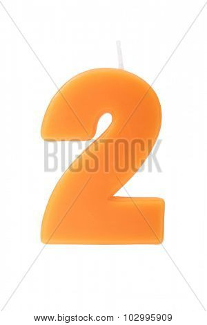 Orange birthday candle in the form of the number two on white background