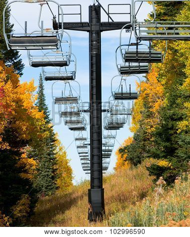 Empty ski lift chairs and fall foliage