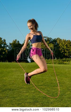 Girl funny jumping on jump rope with a smile.