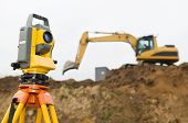 pic of theodolite  - Surveyor equipment theodolite on tripod at building area in front of working construction machinery loader - JPG