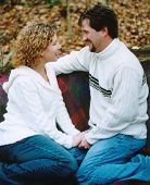 image of love couple  - young couple in love sit and talk in the fall leaves