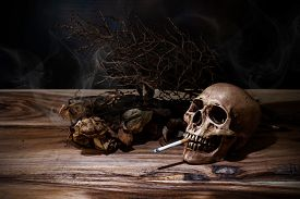 image of tobacco smoke  - Still life Smoking human skull with cigarette on wooden table people smoke cigarette look like trying to commit suicide In the day  - JPG