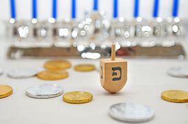 stock photo of hanukkah  - Photo of a dreidel (spinning top) gelts (candy coins) and a silver menorah for Hanukkah isolated on white