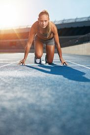 pic of sprinters  - Young woman sprinter in the starter position on a race track at a sports stadium looking up at camera with determination - JPG