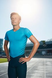 image of sprinters  - Professional man athlete standing with his hands on hips looking off camera into the distance - JPG