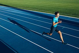 picture of sprinters  - Shot of a young male athlete training on a race track - JPG