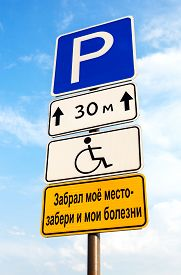 picture of handicapped  - Handicapped parking sign against blue sky - JPG