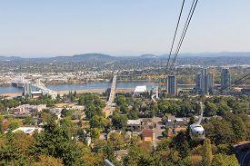 picture of tram  - Portland Aerial Tram Public Transportation above Portland Oregon cityscape with Tilikum Crossing and Ross ISland Bridge over Willamette River - JPG