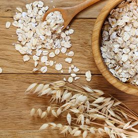 picture of oats  - Rolled oats and oat ears of grain on a wooden table - JPG