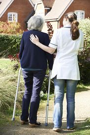 image of zimmer frame  - Carer Helping Senior Woman To Walk In Garden Using Walking Frame - JPG
