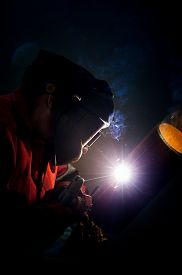 stock photo of pipe-welding  - Welder working in the red uniform and a mask - JPG