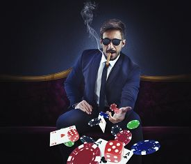 stock photo of gambler  - Rich gambler throws cards dice and chips - JPG