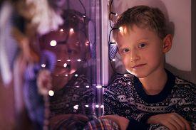 stock photo of sad christmas  - Calm little boy on the windoe with Christmas Lights - JPG