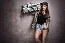 pic of rap-girl  - Teenage girl carrying a ghetto blaster over her shoulder and leaning against a rusty gray wall - JPG