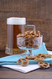 picture of stein  - Glass of beer in stein with mini pretzels on pale blue napkin on wood background - JPG