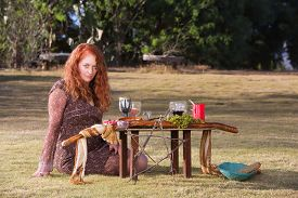 stock photo of sabbatical  - Beautiful priestess in outdoor pagan ritual with altar - JPG