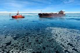 stock photo of fuel tanker  - Red tugboat towing a tanker ship at winter - JPG