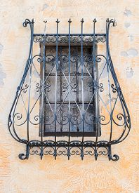 stock photo of grating  - grate of a covered window of an ancient monastery - JPG